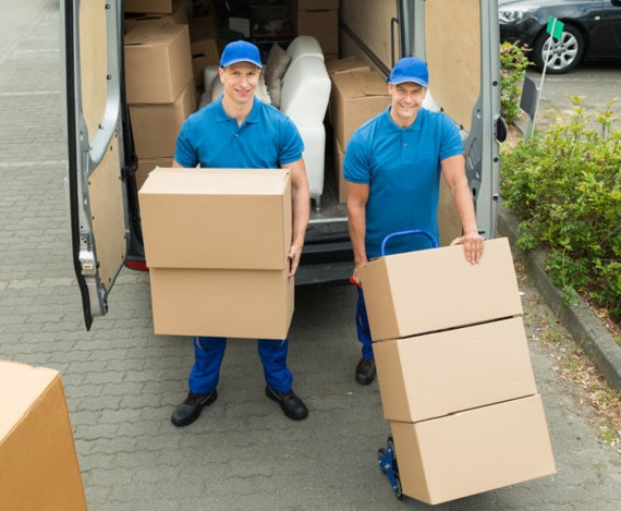42544866 - two happy male workers loading stack of cardboard boxes in truck